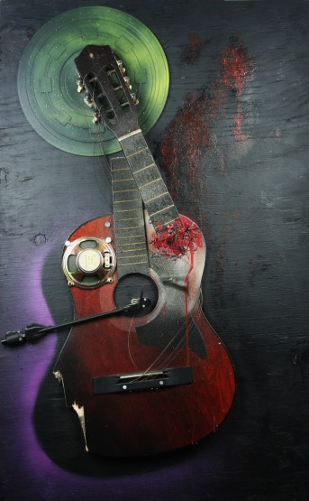 """Christine"" 2010, 24"" x 38"" x 5"" guitar, mixed media on plywood. Christine is a three dimensional assemblage consisting of a warped guitar, a record player's arm and the internal workings of a speaker."